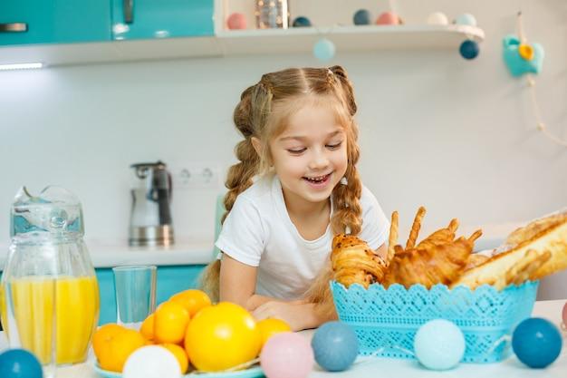 Mała dziewczynka je śniadanie w kuchni z rogalikami i sokiem pomarańczowym.