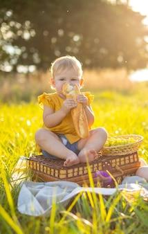 Mała dziewczynka je świeżą bagietkę i owoce na pikniku przy świetle zachodu słońca w przyrodzie