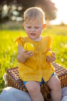 Mała dziewczynka je świeże owoce na pikniku o zachodzie słońca w przyrodzie