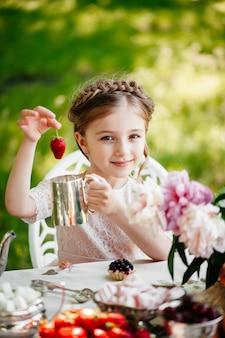 Mała dziewczynka je truskawki w parku