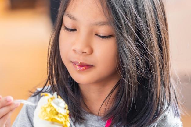 Mała dziewczynka je złocistego liścia lody