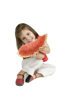 Mała dziewczynka jedzenie arbuza na białym tle