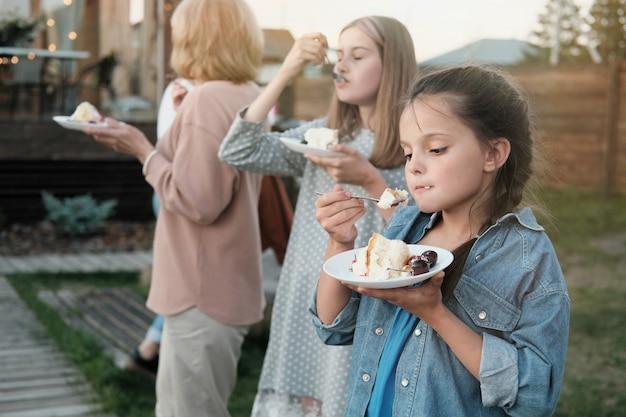 Mała dziewczynka jedzenie ciasta stojąc z rodziną na łonie natury