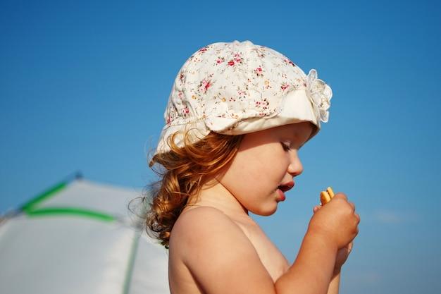 Mała dziewczynka jedzenie ciasteczek na plaży