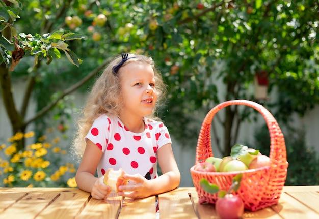 Mała dziewczynka jedzenie dojrzałego jabłka w naturze