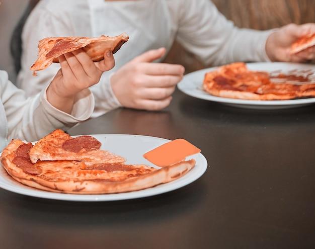 Mała dziewczynka jedzenie pizzy gotowanej w klasie mistrzowskiej