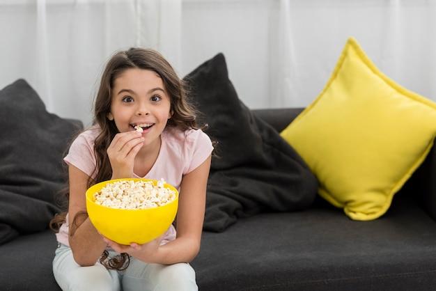 Mała dziewczynka jedzenie popcornu na kanapie
