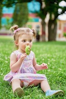 Mała dziewczynka jedzenie pysznego lizaka na zielonym trawniku