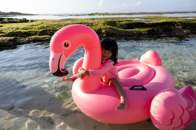 Mała dziewczynka jedzie flaminga unosi się na plaży