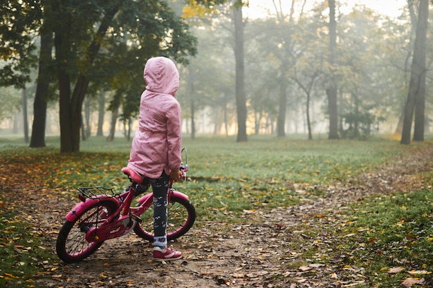 Mała dziewczynka jedzie jej rower na pięknej jesieni mgłowym dniu przy wschodem słońca