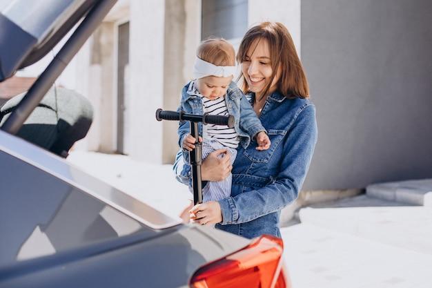 Mała dziewczynka jedzie na skuterze z mamą przy samochodzie