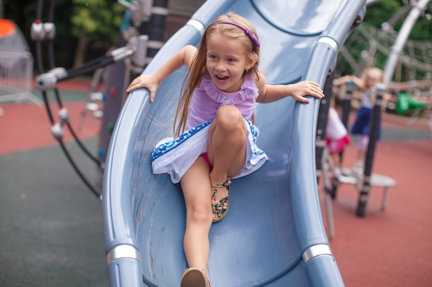 Mała dziewczynka jedzie na wzgórzu w parku rozrywki