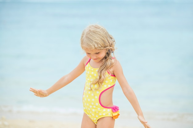 Mała dziewczynka jest piękna i szczęśliwa w jasnym kostiumie kąpielowym po południu na słonecznej plaży