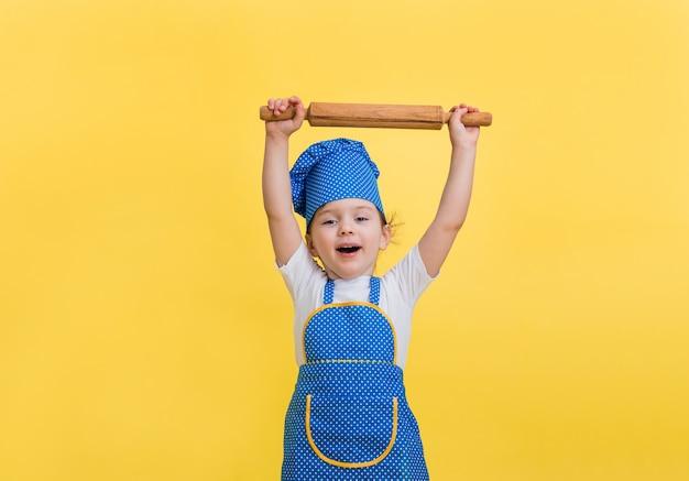 Mała dziewczynka jest szczęśliwa w fartuchu kuchennym i kapeluszu z wałkiem do ciasta na żółtej przestrzeni. szukam