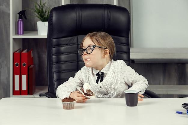 Mała dziewczynka jest szefową, siedzi przy biurku i je babeczkę ubrudzoną śmietaną