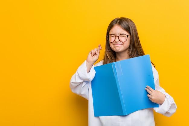 Mała dziewczynka jest ubranym doktorskiego kostium krzyżuje palce dla mieć szczęście