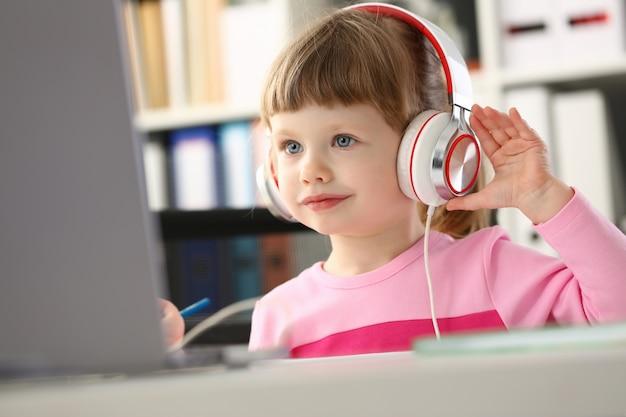 Mała dziewczynka jest ubranym hełmofony używa mobilnego komputer