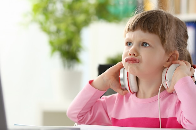 Mała dziewczynka jest ubranym hełmofony używać komputerowy agresywny artykułować