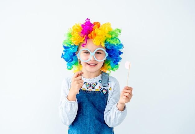 Mała dziewczynka jest ubranym kolorową perukę