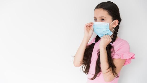 Mała dziewczynka jest ubranym medyczną maskę