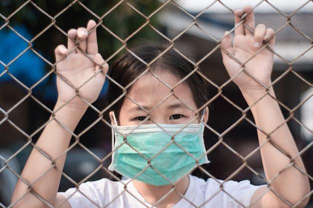 Mała dziewczynka jest ubranym medyczną ochronną maskę w klatce. kwarantanna w celu ochrony koronawirusa.
