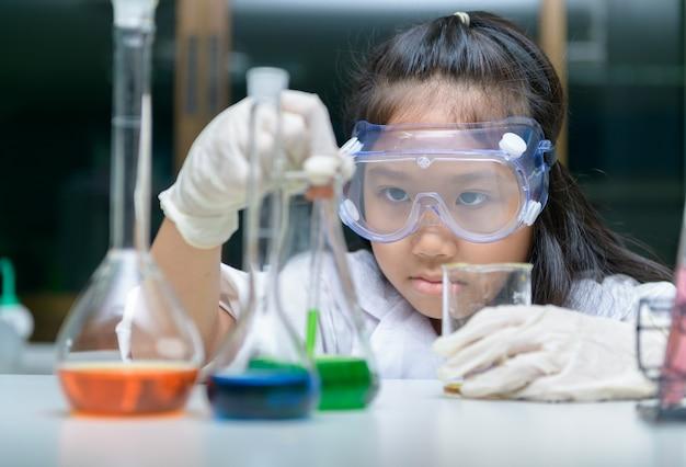 Mała dziewczynka jest ubranym safty gogle robi eksperymentowi
