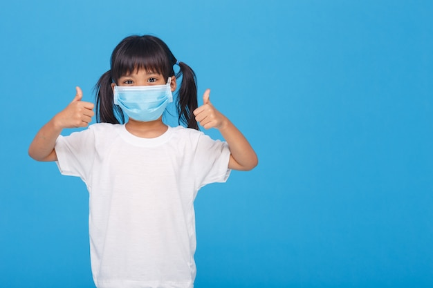 Mała dziewczynka jest ubranym twarzy maskę pokazuje aprobaty