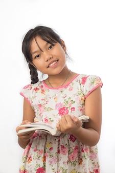Mała dziewczynka jest zadowolona z książki na białym