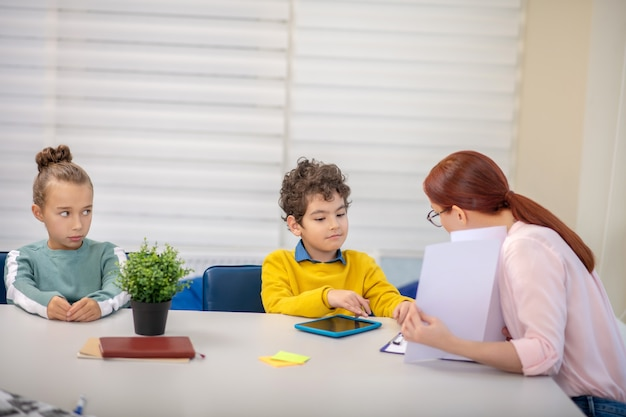 Mała dziewczynka jest zdenerwowana patrząc na swojego kolegę z klasy rozmawiającego z nauczycielem