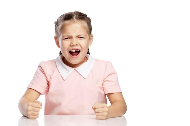 Mała dziewczynka jest zła i krzyczy. pojedynczo na białym tle.