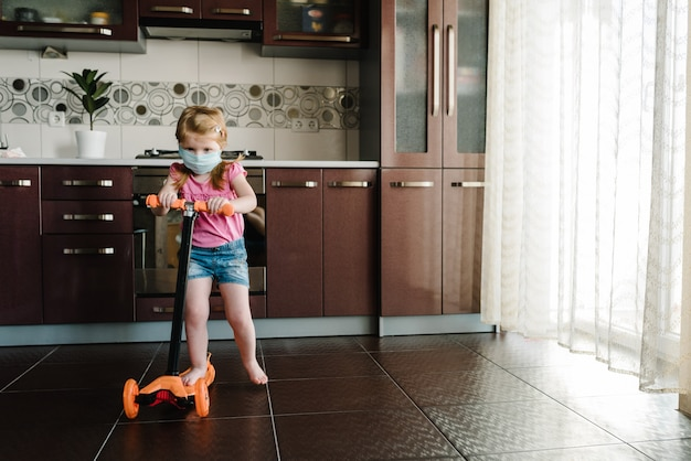 Mała dziewczynka jeździ skuterem. zostań w domu. kampania społecznościowa na rzecz zapobiegania koronawirusom.