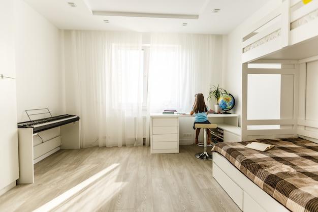 Mała dziewczynka kalkulator i set plastikowa kula ziemska w żywym pokoju