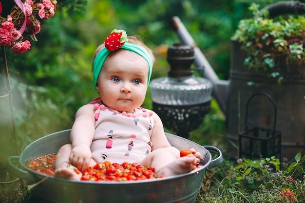 Mała dziewczynka kąpie się w basenie z truskawkami w ogrodzie.
