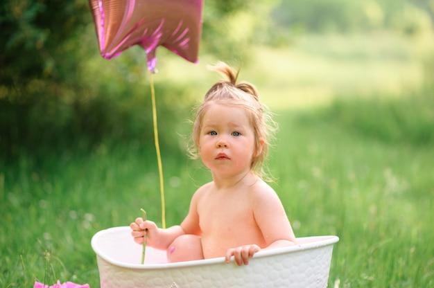 Mała dziewczynka kąpie się w białej małej wannie na zieleni
