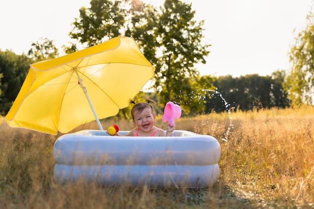 Mała dziewczynka kąpie się w nadmuchiwanym basenie.