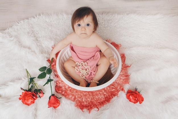 Mała dziewczynka kąpie się w wannie z kwiatami przy kominku. dziecko myje się w misce wśród czerwonych róż.