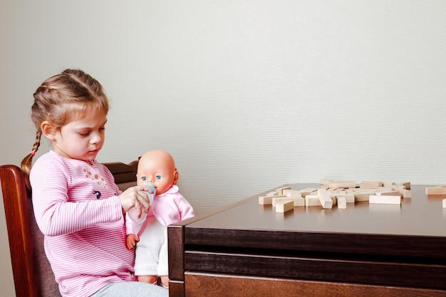 Mała dziewczynka karmi lalkę siedząc przy stole