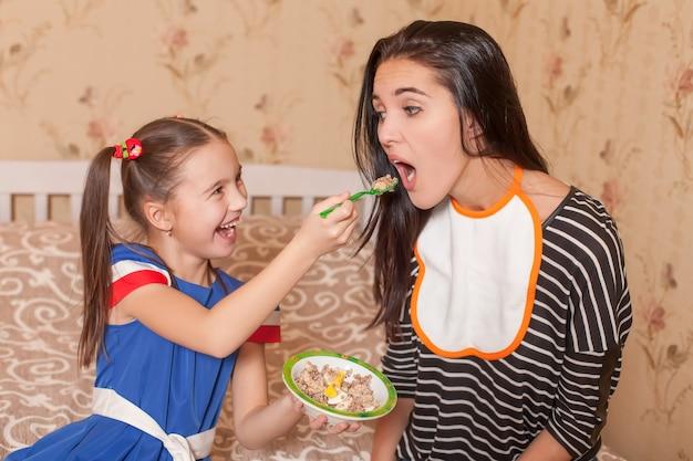 Mała dziewczynka karmi matkę łyżką.