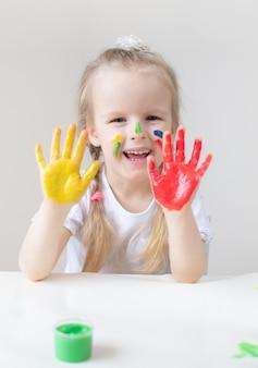 Mała dziewczynka kaukaska malująca kolorowymi rękami maluje w domu wczesna edukacja przygotowywa do przedszkola rozwój dzieci gra