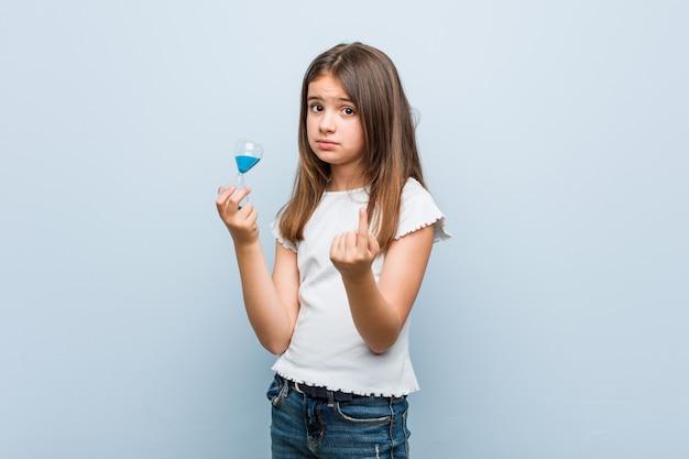 Mała dziewczynka kaukaska trzyma klepsydrę wskazującą na ciebie palcem, jakby zapraszając podchodzi bliżej.