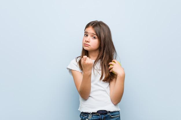 Mała dziewczynka kaukaska trzyma zielone jabłko wskazujące palcem na ciebie, jakby zapraszając podchodzi bliżej.