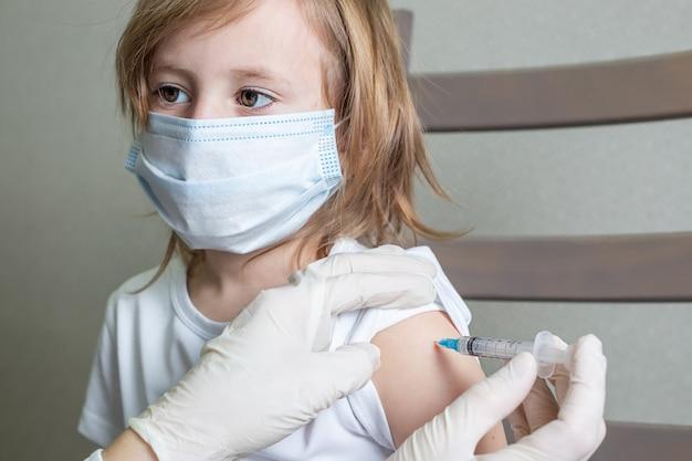 Mała dziewczynka kaukaska w masce medycznej siedzi na krześle w kabinie lekarza i otrzymuje szczepionkę, patrzy na lekarza