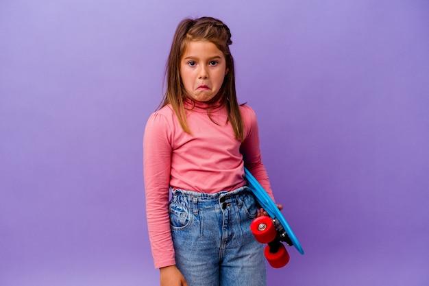 Mała dziewczynka kaukaski figurowa na białym tle na niebieskiej ścianie wzrusza ramionami i zdezorientowana otwartymi oczami.