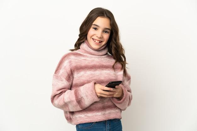 Mała dziewczynka kaukaski na białej ścianie, wysyłając wiadomość z telefonu komórkowego