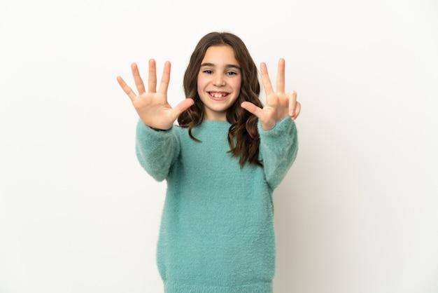 Mała dziewczynka kaukaski na białym tle na białej ścianie, licząc osiem palcami
