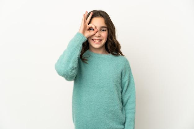 Mała dziewczynka kaukaski na białym tle na białej ścianie pokazuje znak ok palcami