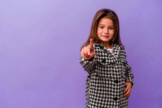 Mała dziewczynka kaukaski na białym tle na fioletowej ścianie pokazuje numer jeden z palcem.
