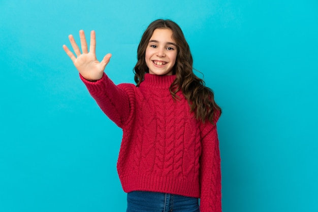 Mała dziewczynka kaukaski na białym tle na niebieskiej ścianie, licząc pięć palcami