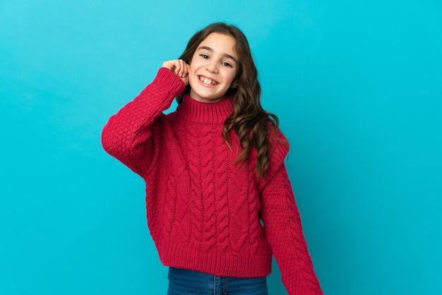 Mała dziewczynka kaukaski na białym tle na niebieskiej ścianie, śmiejąc się