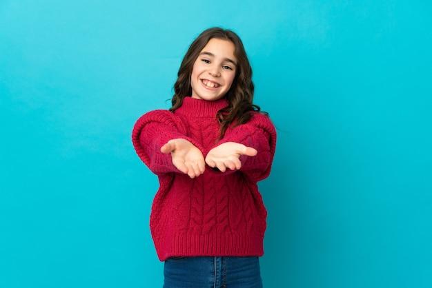 Mała dziewczynka kaukaski na białym tle na niebieskiej ścianie trzymając copyspace wyimaginowany na dłoni, aby wstawić reklamę